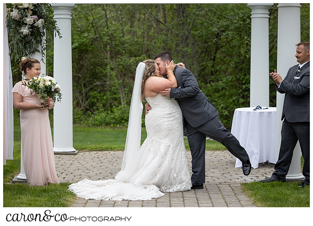 a groom reaches in for the first kiss in front of the pergola at a Landing at Pine Point Maine wedding ceremony