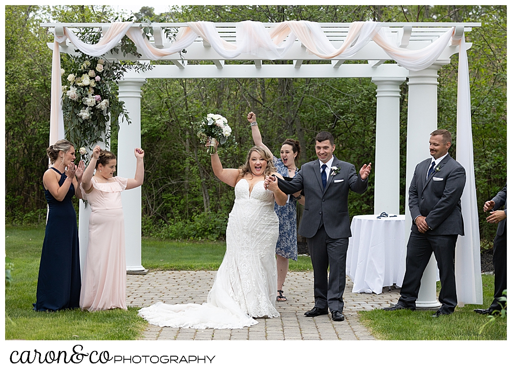 a bride and groom raise their arms to cheer their marriage as they stand in front of the pergola at the Landing at Pine Point, Scarborough, Maine