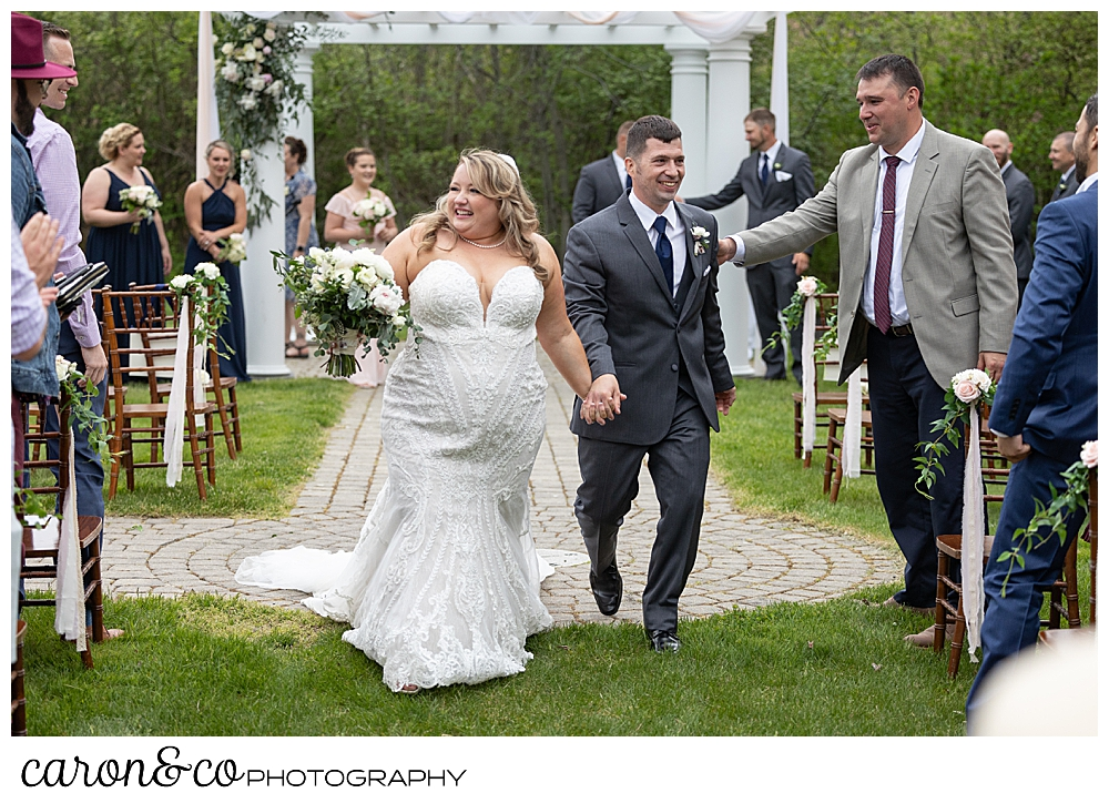 a bride and groom acknowledging their guests during their recessional at their Pine Point Maine wedding ceremony
