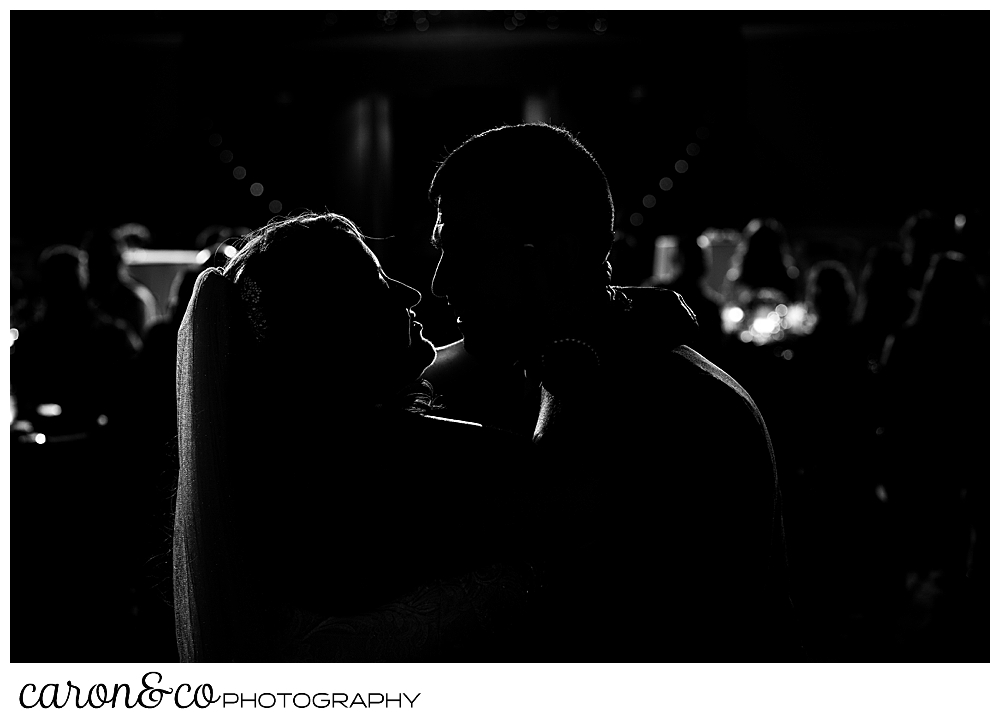 a black and white silhouette of a bride and groom during their first dance