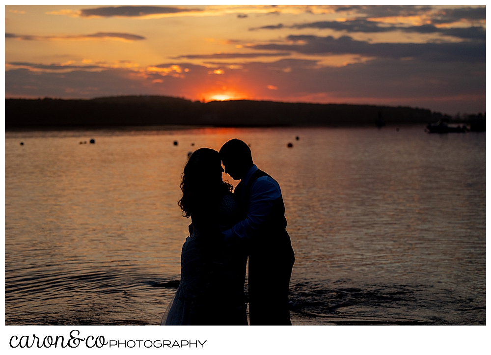 a silhouette of a bride and groom during a gorgeous sunset at their Pine Point Maine wedding