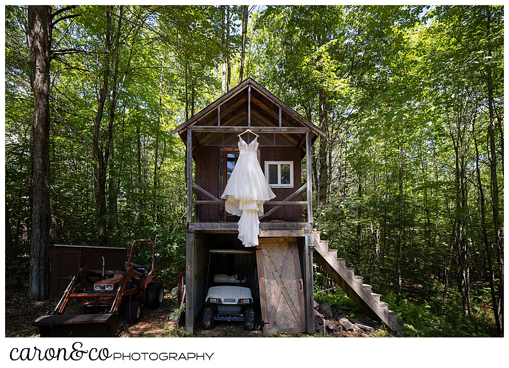 wedding dress hanging from a two story building, child's playhouse on top, storage on bottom,