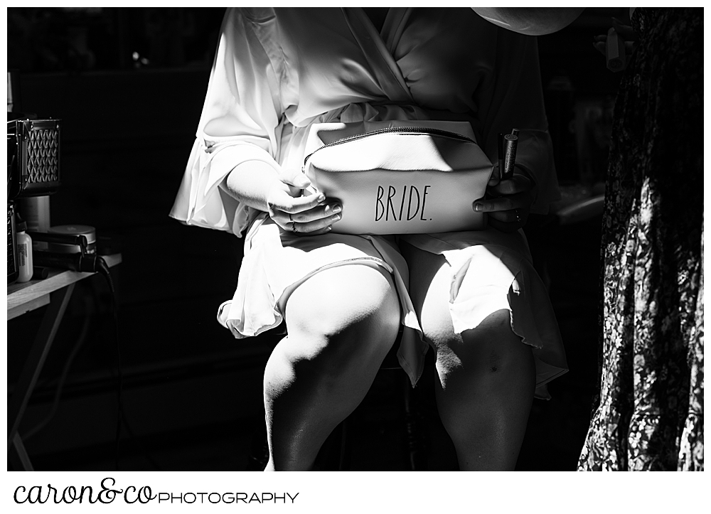 black and white photo of a bride, wearing a robe as she sits in a chair getting her makeup done. She's holding a toiletry bag that says bride