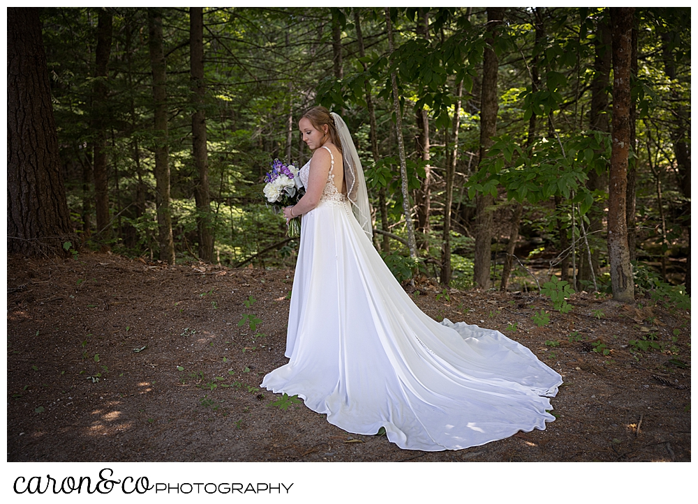 full length bridal portrait of a bride in the woods, she has a long train, and a short veil