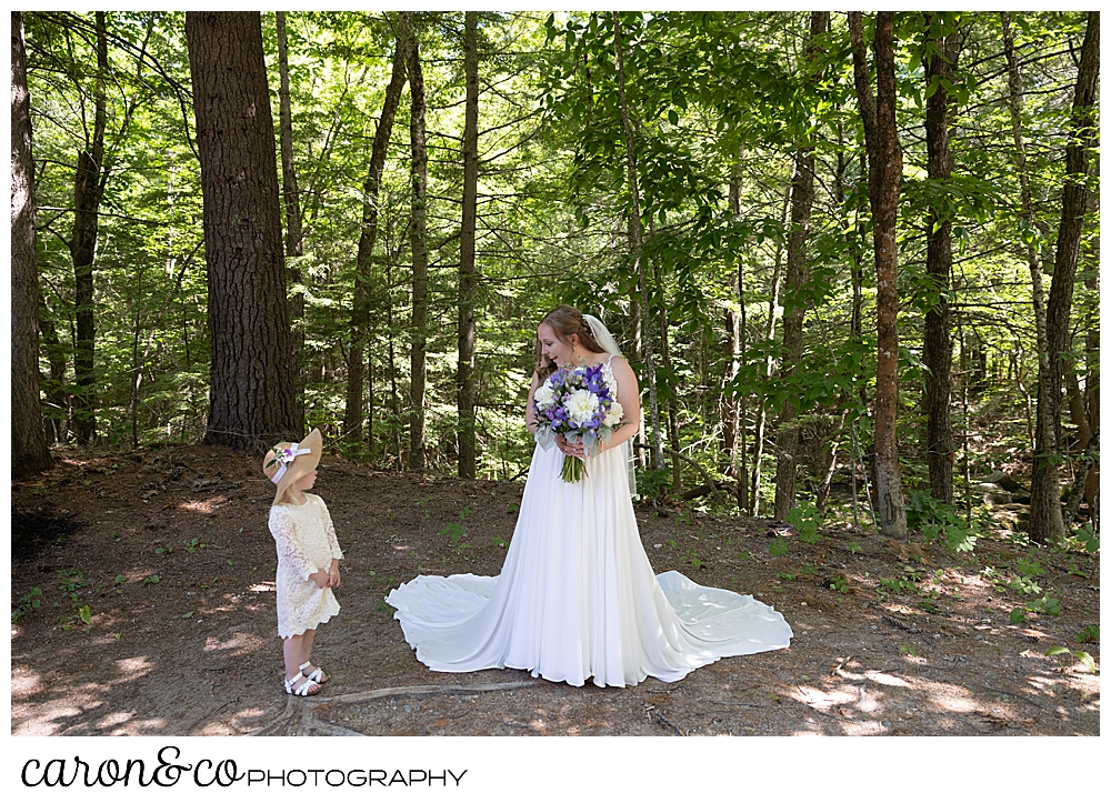 a beautiful Maine bride, standing with her dress flowing around her, smiling at a tiny flower girl wearing a white lace dress, and a straw hat