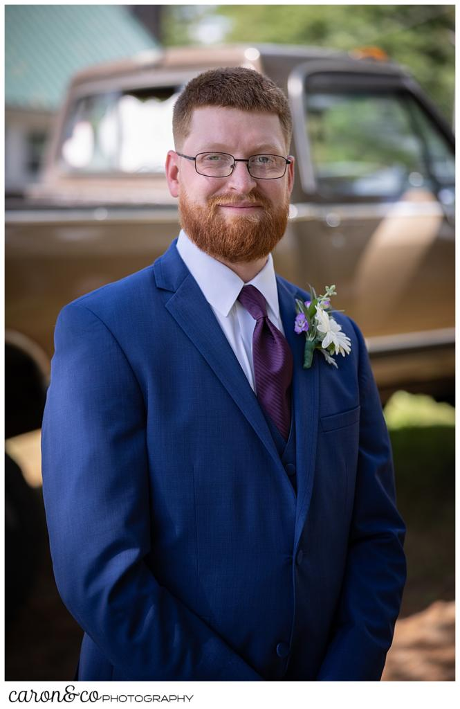 groom portrait, red haired groom wearing a blue suit, standing in front of his vintage pickup truck