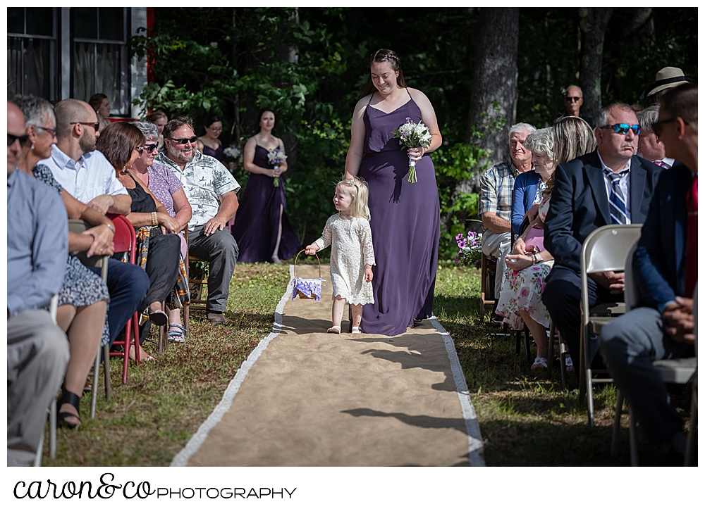 a bridesmaid in purple, walks down a burlap runner, with a tiny flower girl in a white lace dress