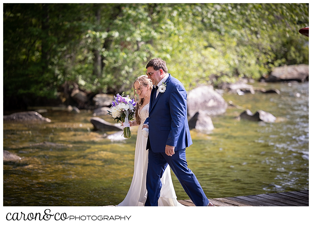 a bride and her dad are walking towards the aisle at a highland lake maine wedding ceremony