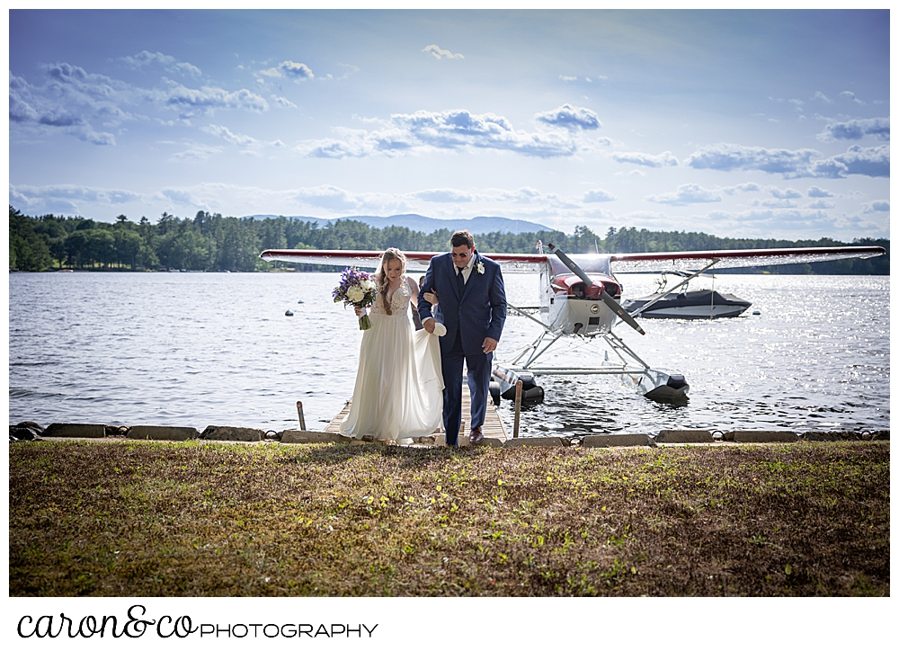 a bride and her dad step out of a sea plane, and begin to walk down the aisle, at a highland lake maine wedding highland lake maine wedding