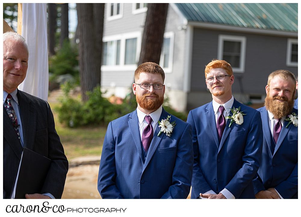 an officiant, dressed in black; and a groom, and best man dressed in blue, await the bride and her father
