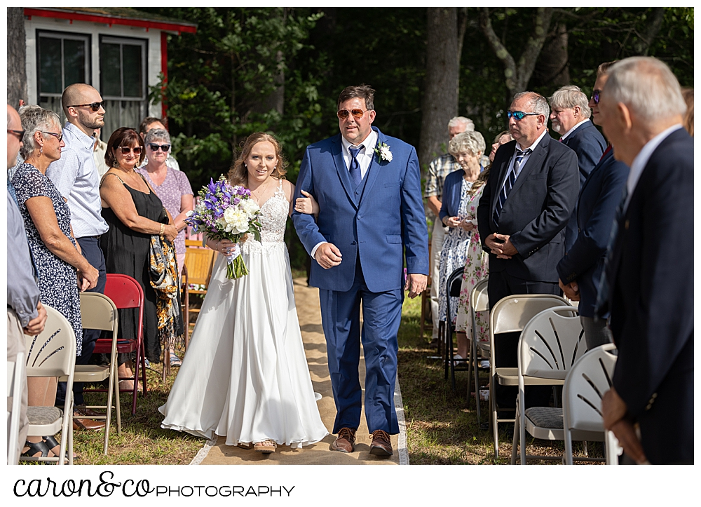 a bride in white, and her dad in blue, walk down the aisle, at a Highland Lake Maine wedding ceremony