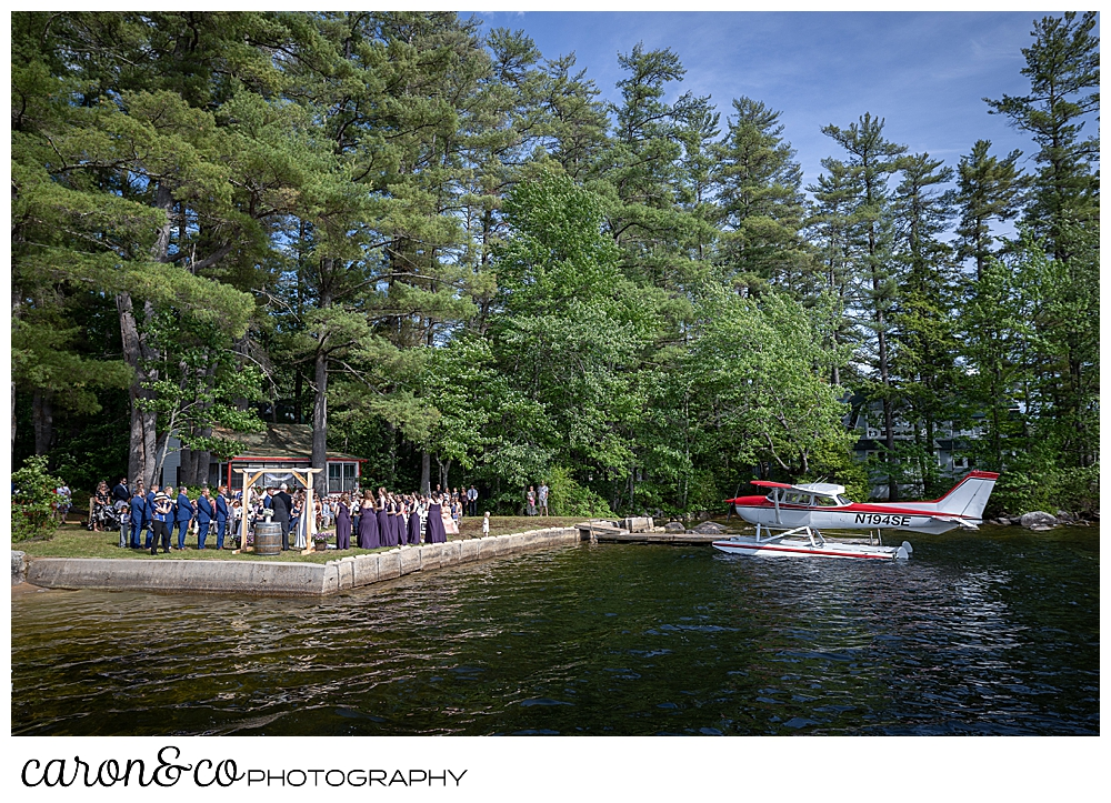 wide view of a Highland Lake Maine wedding ceremony, with a sea plane on the dock