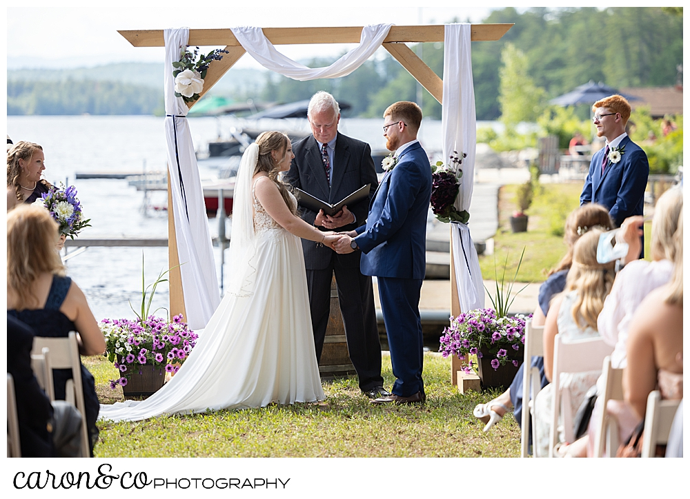 bride and groom standing before an officiant at their highland lake maine wedding ceremony