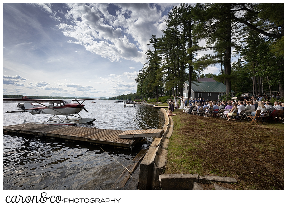 a highland lake wedding ceremony with a sea plane at the dock, Bridgton Maine wedding photographers
