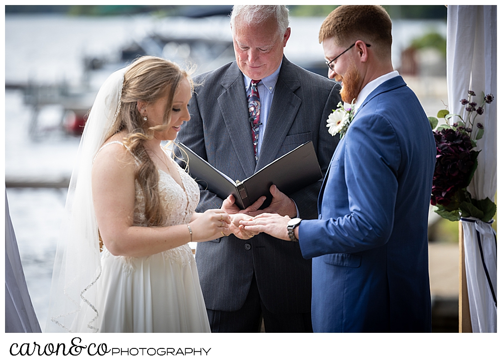 bride putting ring on groom's finger during their highland lake maine wedding ceremony