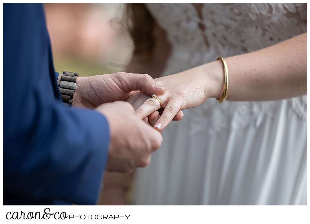 groom putting ring on bride's finger during their highland lake maine wedding ceremony