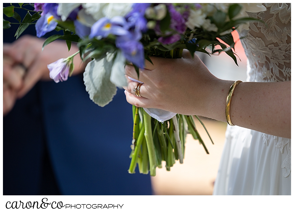 bride's hand with her new wedding band, holding a bouquet of purple, blue, white, and green flowers, at a highland lake maine wedding