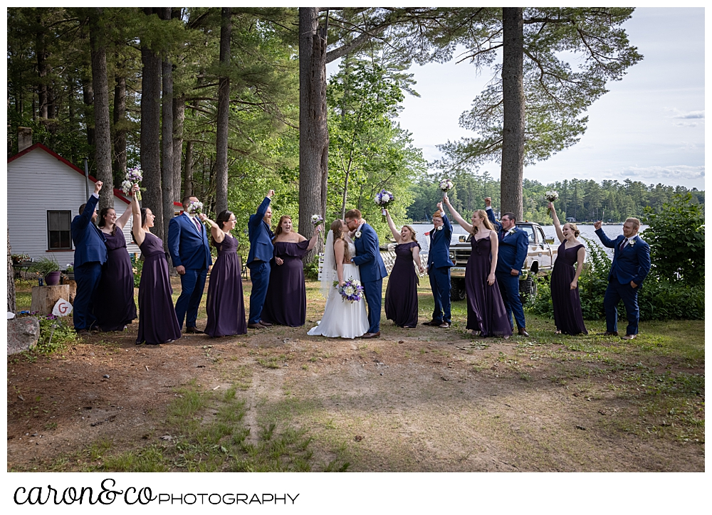 a bride and groom pose with their wedding party, the bridesmaids are dressed in purple, the men in blue, they're loosely grouped together at a highland lake maine wedding ceremony