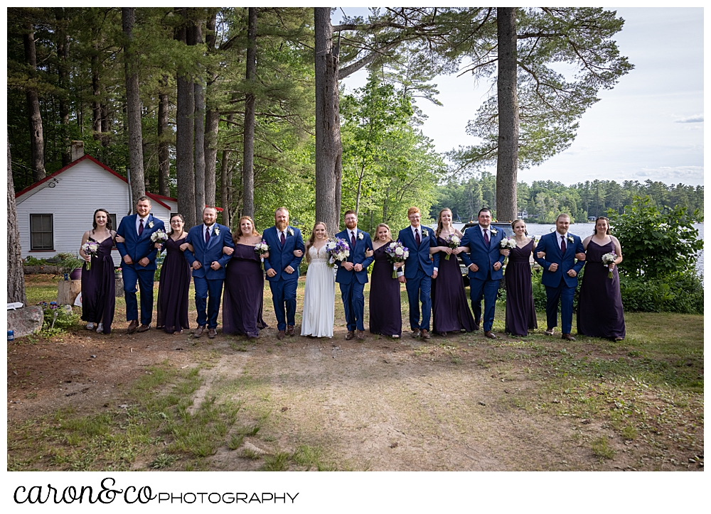 a bridal party with linked arms, walking towards the camera, women are in dark purple, men in blue, at a highland lake maine wedding