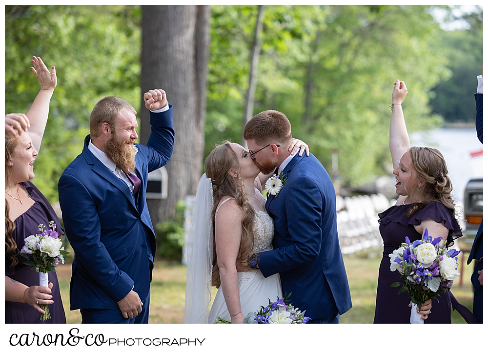 a bride and groom kiss as their wedding party looks on and cheers, at a highland lake maine wedding