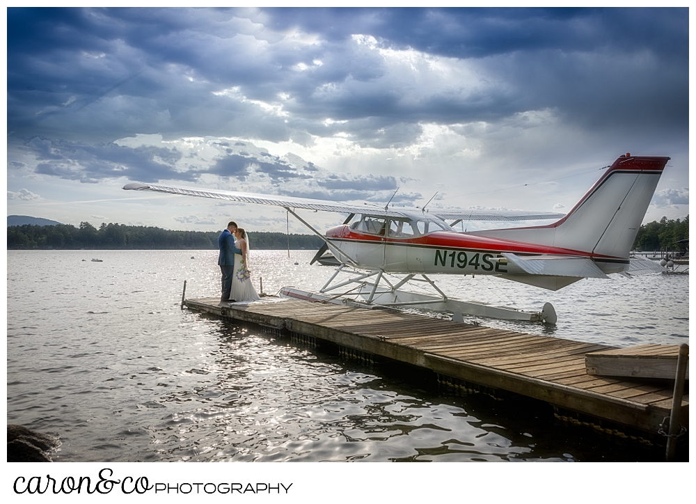 a bride and groom standing on the end of a dock, kissing, with a sea plane in the background, at their highland lake maine wedding