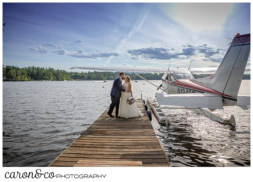 bride and groom kissing on a dock, with a sea plane in the background, at their highland lake maine wedding