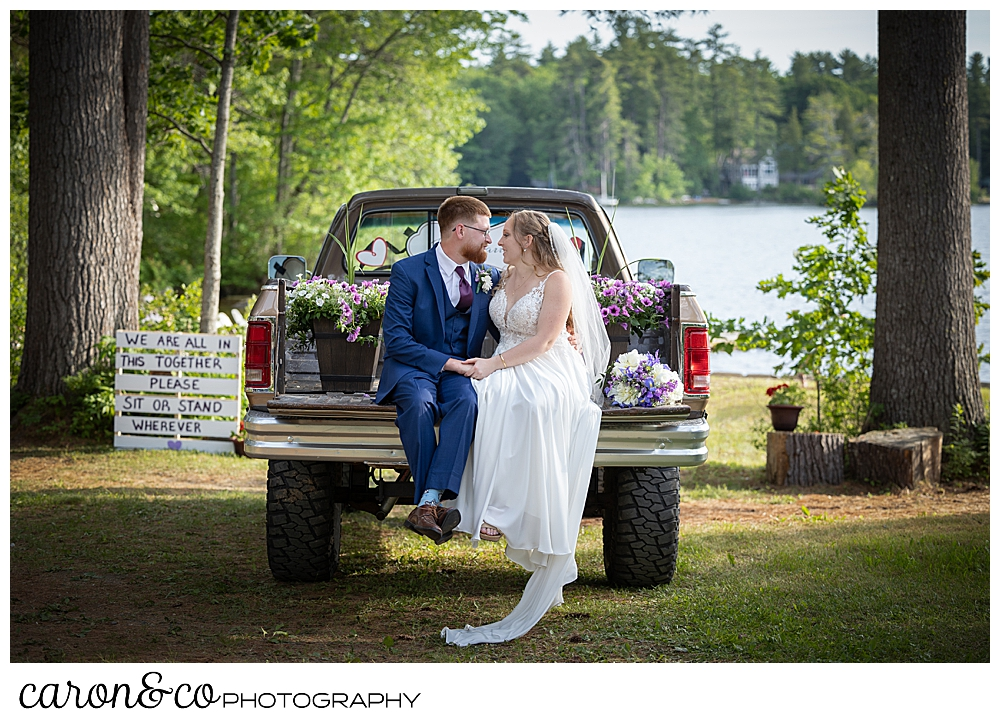 a bride and groom sit on the tailgate of a vintage truck at their highland lake maine wedding