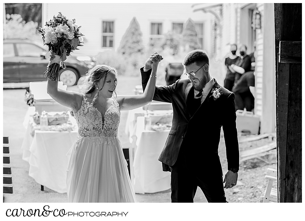 black and white photo of a bride and groom entering their reception