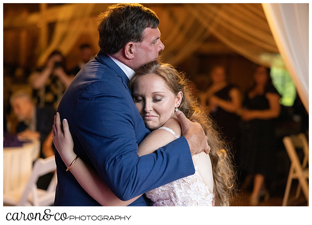 bride and her father hugging during the father daughter dance at their highland lake Maine wedding reception