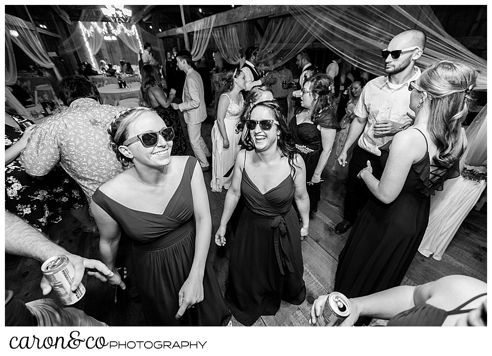 black and white photo of guests wearing sunglasses on the dance floor during a Harrison Maine wedding reception
