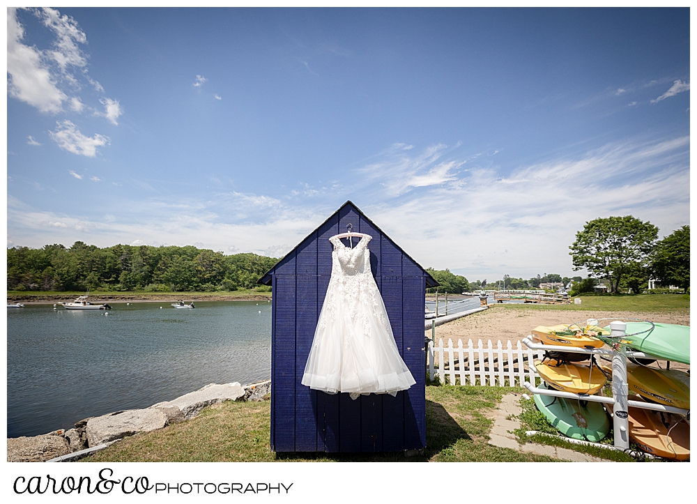 a wedding dress hangs from a purple shed on the Kennebunk River, Kennebunkport, Maine