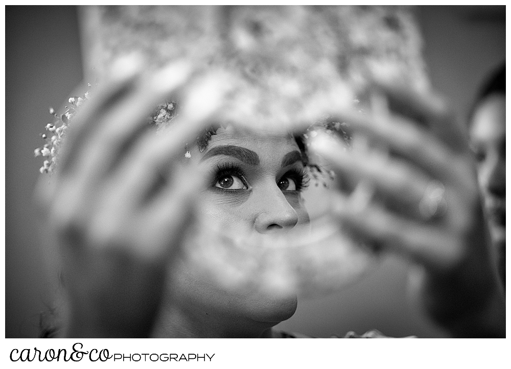 black and white photo of a bride holding a mirror, her eyes are peeking through the handle of the mirror
