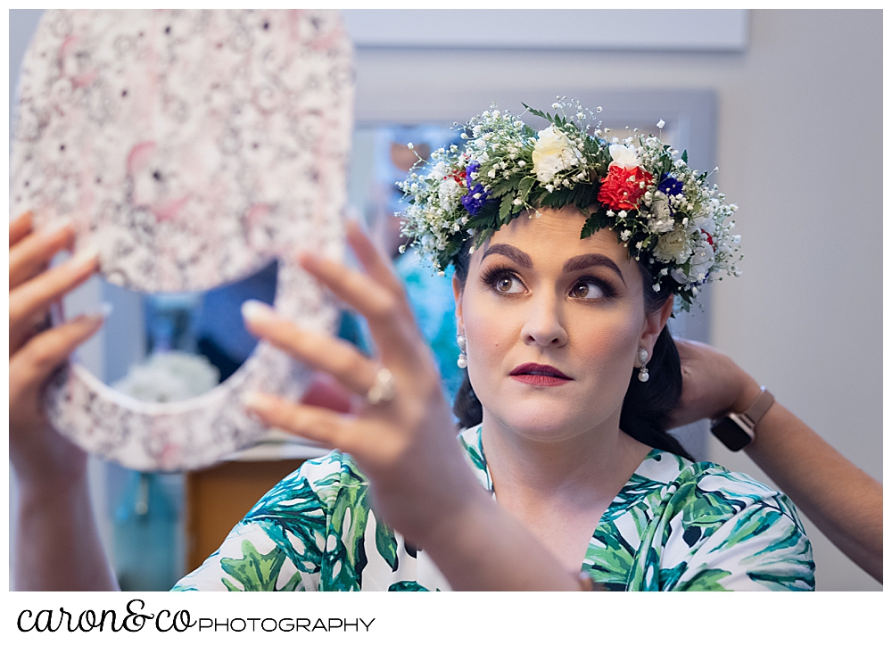a bride holds a mirror, while she checks her flowered headpiece