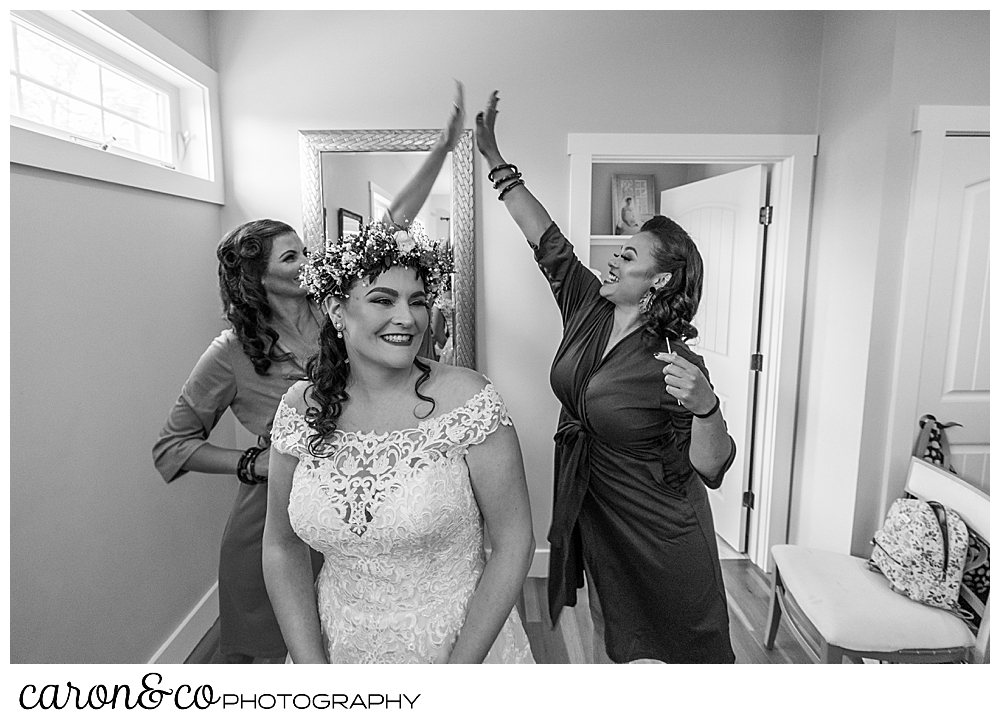 black and white photo of bridesmaids giving each other a high five behind a bride who's laughing