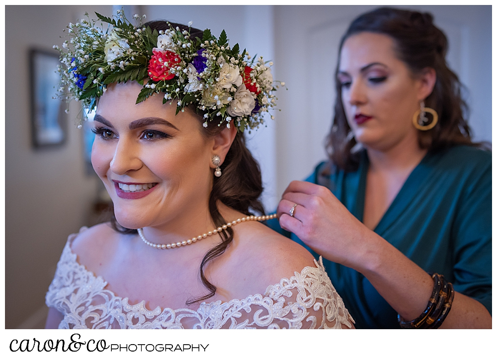 a bridesmaid helps a bride put on a string of pearls