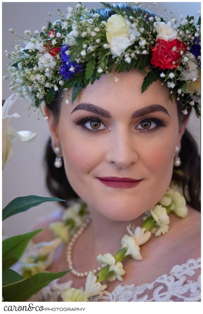 beautiful bridal portrait of a dark haired bride, wearing a flowered headpiece, and a white lei
