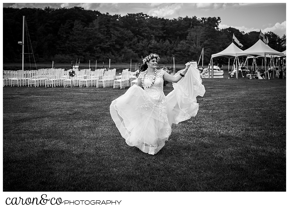 black and white photo of a bride walking around her outdoor ceremony venue at a Nonantum Resort tented wedding, Kennebunkport, Maine