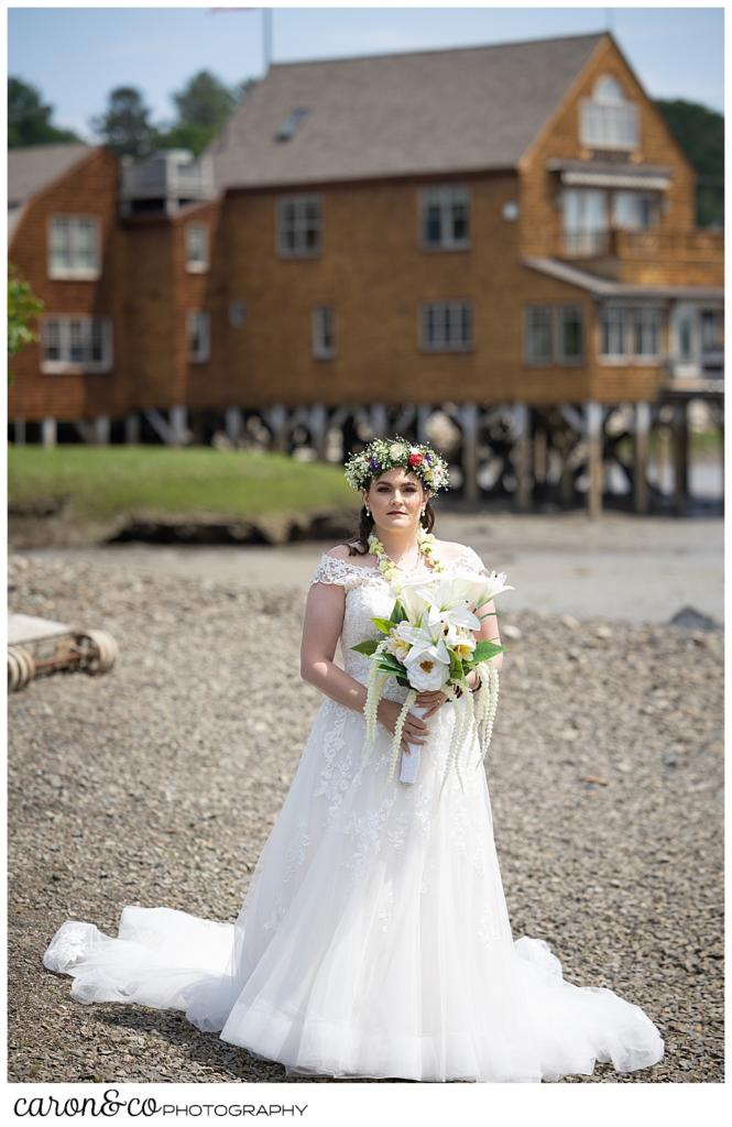 a full length photo of a bride waiting to do a Nonantum Resort tented wedding first look, there is a brown house in the background