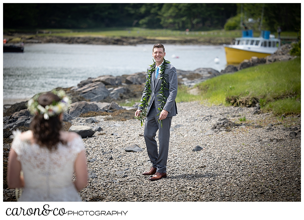 a groom wearing a gray suit, turns to see his bride during a Nonantum Resort tented wedding first look