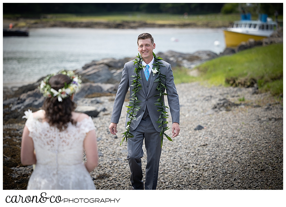 a groom wearing a gray suit, walks towards his bride, during a Nonantum Resort tented wedding first look