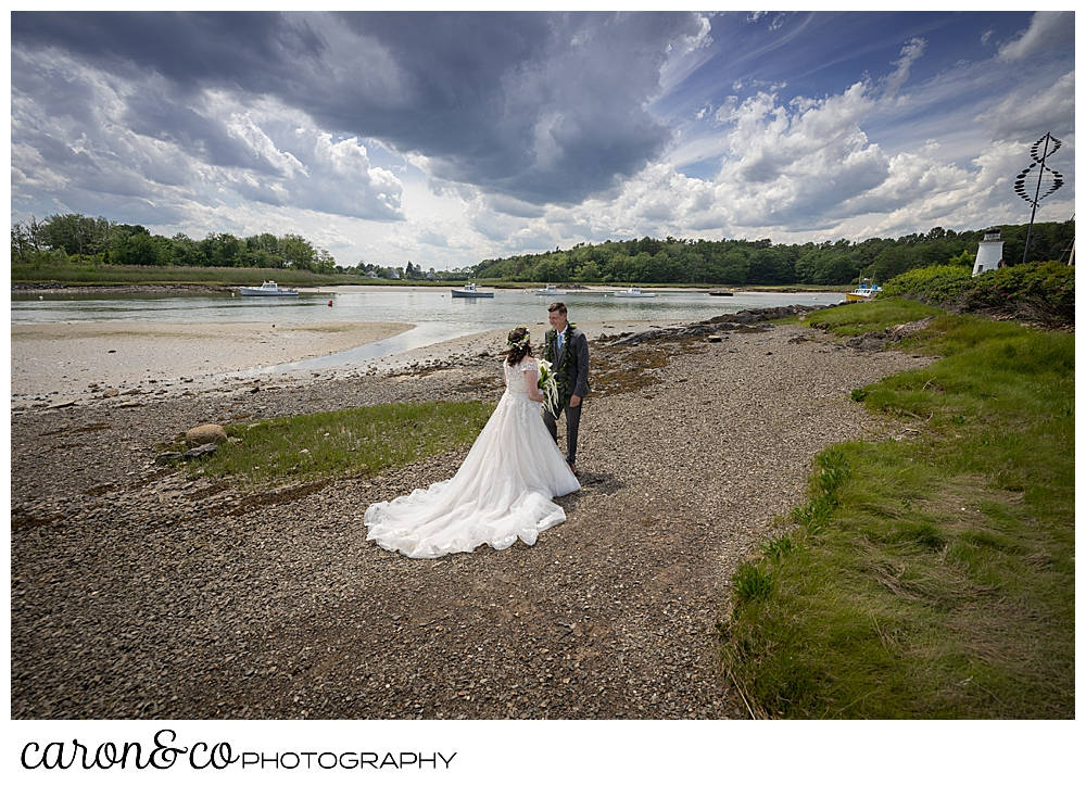 a bride and groom on the banks of the Kennebunk River, during a wedding day first look, at a Nonantum Resort tented wedding