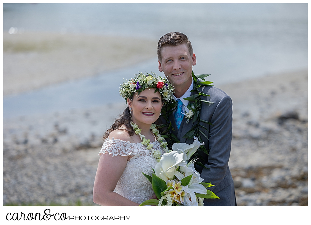 a beautiful portrait of a bride and groom, the bride is wearing a white dress, a flowered headpiece, and a white lei; the groom is wearing a gray suit, a blue tie, and a green lei