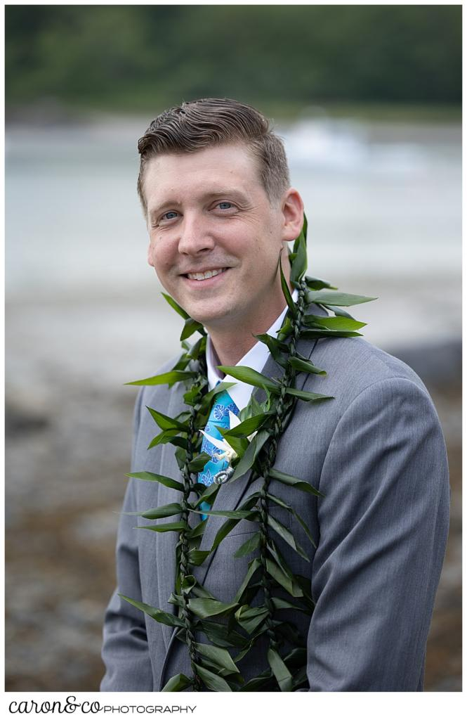 groom portrait of a groom wearing a gray suit, a blue tie, and a green lei