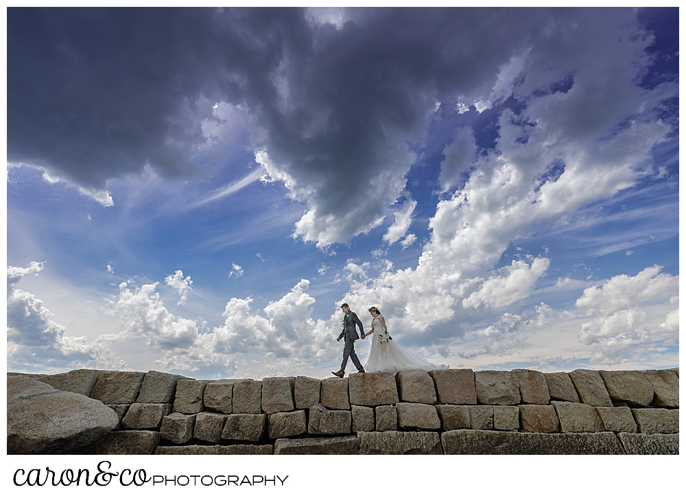 a bride and groom walk hand in hand along the Kennebunkport Breakwater, Kennebunkport, Maine