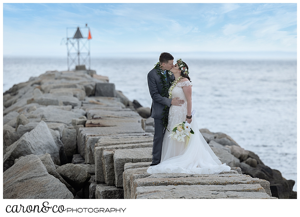 a bride and groom kiss on the top of the Kennebunkport Breakwater, Kennebunkport, Maine
