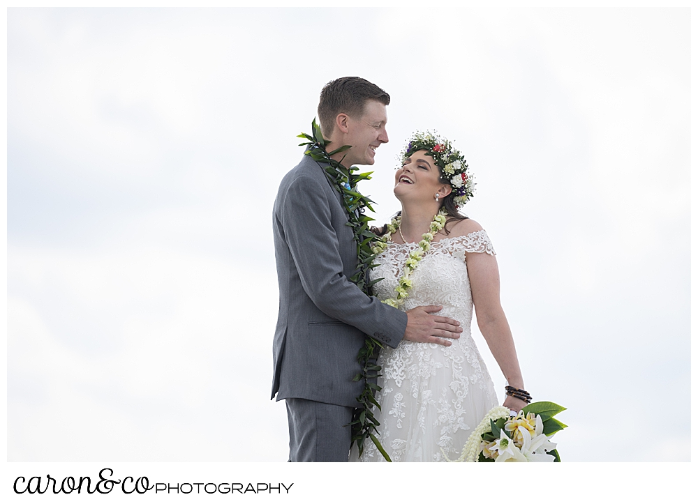 a bride and groom stand together, smiling and talking