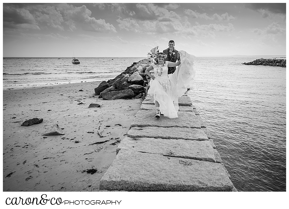 black and white photo of a bride and groom walking on the Kennebunkport Breakwater, the bride is holding her dress