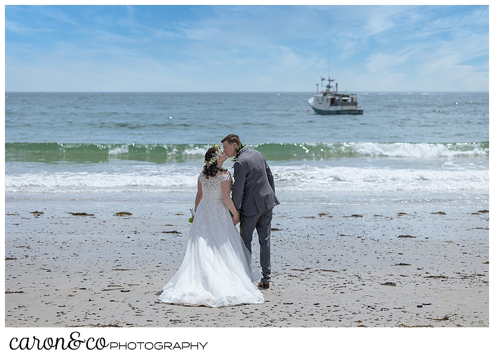 a bride and groom kiss, their backs to the camera, as they stroll on Colony Beach, Kennebunkport, Maine