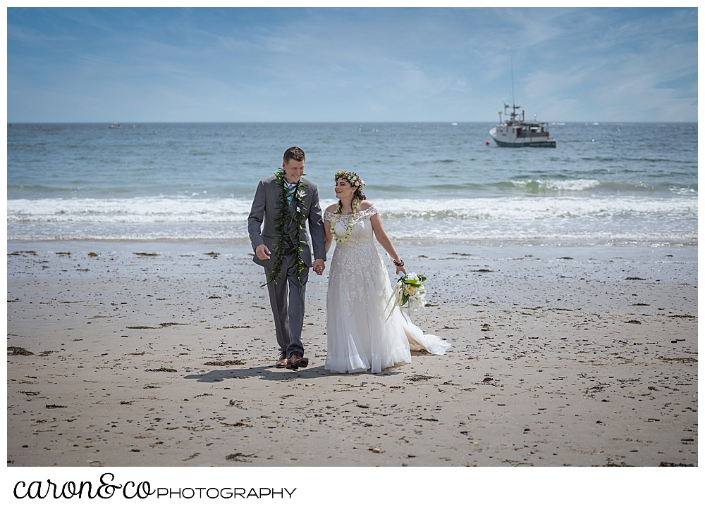 a bride and groom walk towards the camera on Colony Beach, Kennebunkport, Maine