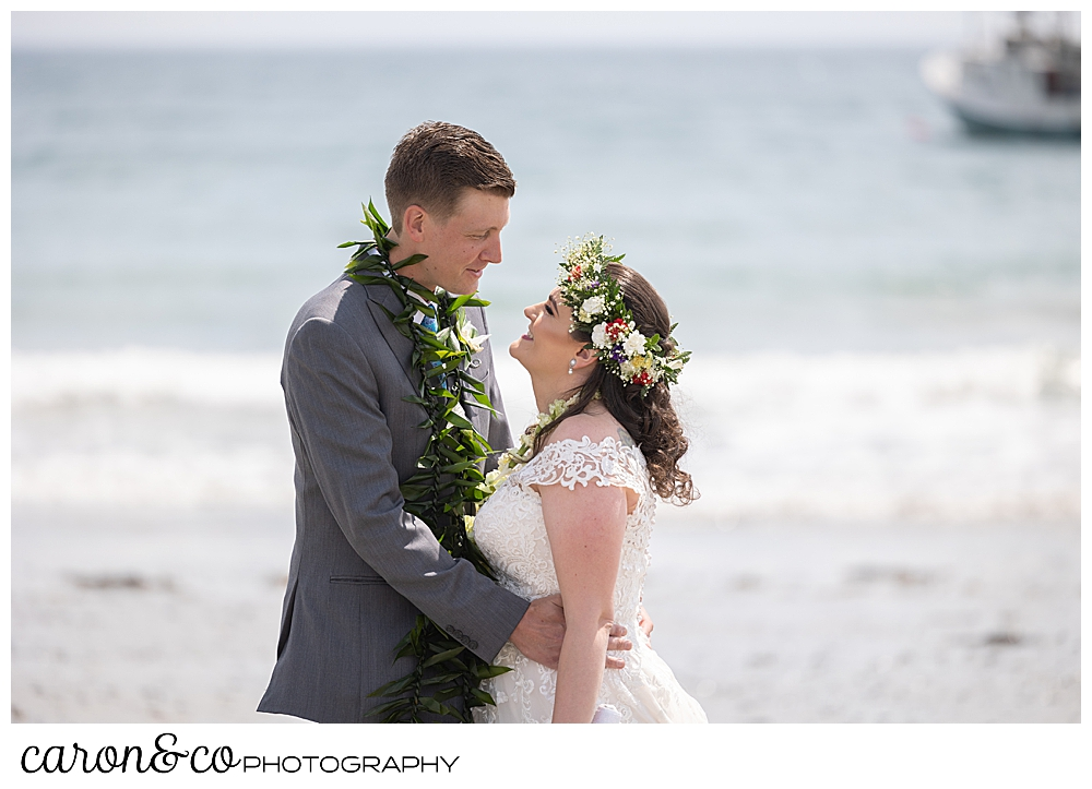 a bride and groom hug each other face to face on Colony Beach, Kennebunkport, Maine